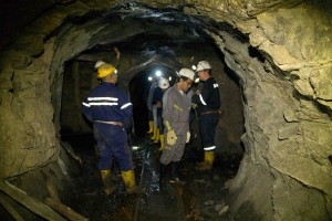 Inside a Colombian mine. Tim Moore (far right) discusses with colleagues the geology of the mine.